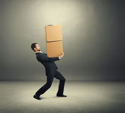 Tired businessman carrying two boxes Stock Images