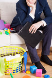 Tired businessman cleans up the mess in the house Stock Images