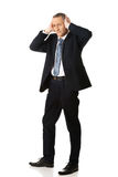 Tired businessman covering ears with hands Royalty Free Stock Photo