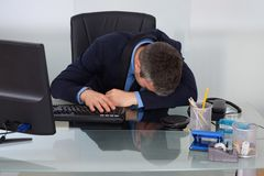 Tired businessman at desk Royalty Free Stock Photos
