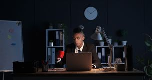 Tired businessman drinking coffee and working on laptop at night. Tired african american businessman drinking coffee and working on laptop late in night office stock footage