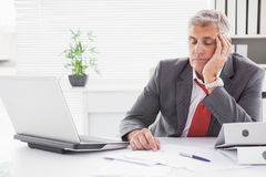 Tired businessman falling asleep at desk. In his office Stock Image