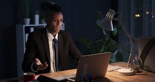 Tired businessman frustrated with laptop problem late in night. Tired african american businessman frustrated with laptop problem at night office stock footage