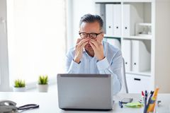 Tired businessman in glasses with laptop at office. Business, overwork, deadline and people concept - tired businessman in eyeglasses with laptop computer Royalty Free Stock Photos