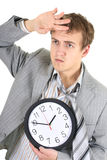 Tired businessman in grey suit holding a clock Royalty Free Stock Images