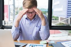Tired businessman with hand on forehead at office. frustrated ma. Tired businessman with hand on forehead at office. frustrated young man with headache at Stock Photos