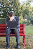 Tired businessman with laptop. Sitting on a park bench Stock Images