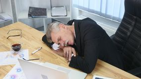 Tired businessman with laptop falling asleep in office.  stock image