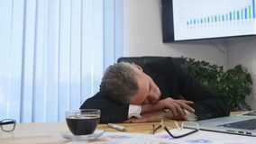 Tired businessman with laptop falling asleep in office.  stock images