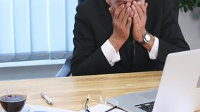 Tired businessman with laptop falling asleep in office.  royalty free stock photo