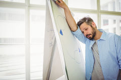 Tired businessman leaning on whiteboard in office Royalty Free Stock Photography