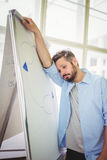 Tired businessman leaning on whiteboard in office Stock Photos