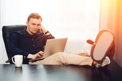 Tired businessman with legs to desk and laptop on knees Royalty Free Stock Photos