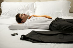 Tired Businessman Lying on Bed Royalty Free Stock Image