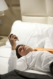 Tired Businessman Lying on Bed Stock Photography