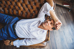 Tired businessman lying on couch stock photos