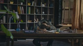 Tired businessman lying on desk at office. Exausted man on desk at workplace. Tired businessman lying on desk in home office. Frustrated business man lying head stock video