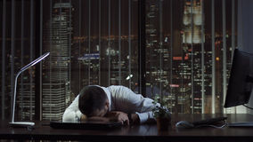 Exhausted man sleeping in office. Tired businessman lying and sleeping on desk in office at night Stock Image