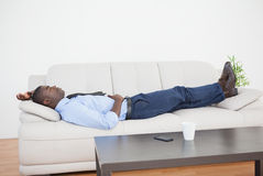 Tired businessman lying on the sofa Royalty Free Stock Images
