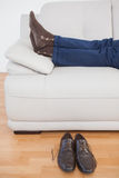 Tired businessman lying on sofa with shoes off Stock Images
