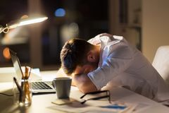 Tired businessman lying on table at night office. Business, overwork, deadline and people concept - tired businessman lying on table at night office Royalty Free Stock Image
