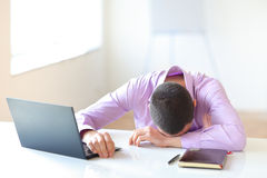 Tired businessman lying on the table Royalty Free Stock Images