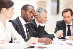 Tired businessman during meeting Stock Photos