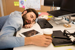 Tired businessman napping on desk in creative office Royalty Free Stock Image