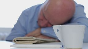 Tired Businessman Napping at Home with Coffee and Newspaper on the Table royalty free stock photography