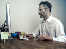 Tired businessman at night office. Overwork, deadline business concept, businessman typing on computer at night office Royalty Free Stock Image