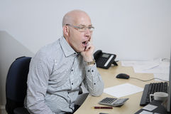 Tired businessman in office. At his desk Royalty Free Stock Photography