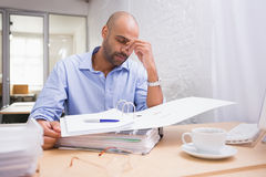 Tired businessman with paperwork at desk Royalty Free Stock Photography
