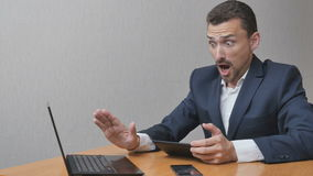 Tired businessman pushes away electronic devices. Man is tired of gadgets. A person is freed from dependence on high technologies. Stop online and hello stock footage