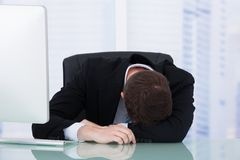 Tired businessman resting at office desk Stock Image