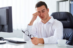 Tired businessman rubbing his eye. Young tired businessman rubbing his eye in the office Stock Images