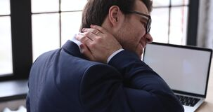 Tired businessman rubbing stiff sore neck tensed muscles in office