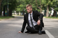 Tired Businessman Sitting on Asphalt Outdoors In Park Royalty Free Stock Photography