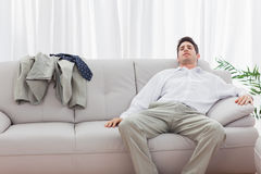 Tired businessman sitting back on sofa Royalty Free Stock Images