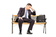 Tired businessman sitting on a bench. Isolated on white background Stock Photos