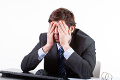 Tired businessman sitting at the desk Stock Photo