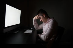 Tired businessman sitting and sleeping in front of computer in night office Royalty Free Stock Photo