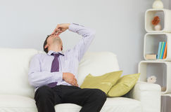 Tired businessman sitting on sofa in living room Royalty Free Stock Image
