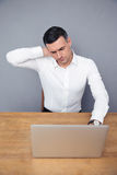 Tired businessman sitting at the table with laptop Royalty Free Stock Image