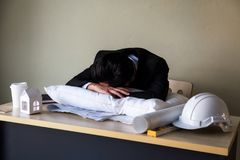 Tired businessman sleep on pillow at office table Stock Photos