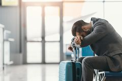 Tired businessman sleeping at airport lobby while waiting. For flight stock images