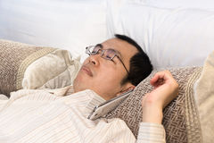 Tired businessman sleeping on bed Royalty Free Stock Photos
