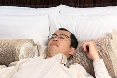 Tired businessman sleeping on bed Royalty Free Stock Image