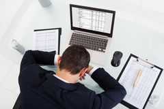 Tired businessman sleeping while calculating expenses in office Stock Image