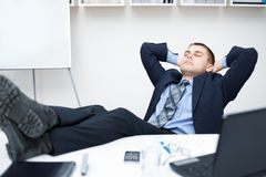 Tired businessman sleeping on chair in office Stock Image