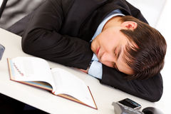 Tired businessman sleeping at desk in  office Stock Image